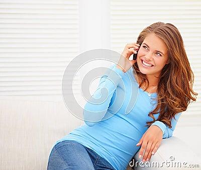 Jeune fille teenaged heureuse parlant au-dessus du téléphone