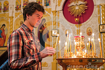 Jeune homme allumant une bougie dans l église.