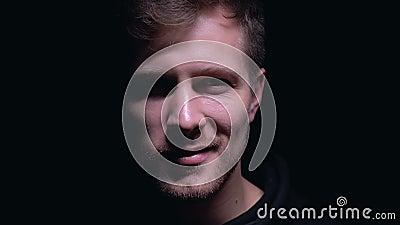 Jeune homme avec le sourire fou regardant la caméra d'isolement sur le fond foncé, psychopathe clips vidéos