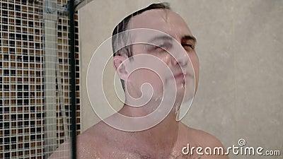 Jeune homme beau prenant la douche dans la salle de bains d'hôtel Soin de fuselage Arrosez circuler banque de vidéos