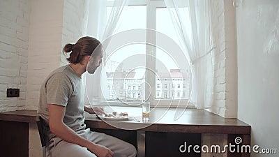 Jeune homme buvant la maison de Juice And Having Breakfast At banque de vidéos