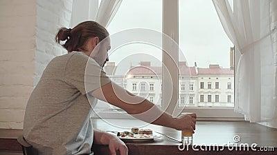 Jeune homme buvant la maison de Juice And Having Breakfast At clips vidéos
