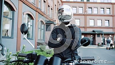 Jeune homme et cycliste en casque sur moto en ville avec un arrière-plan urbain banque de vidéos