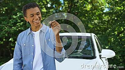 Jeune homme noir tenant une clé d'automobile, achat de transport, permis de conduire banque de vidéos