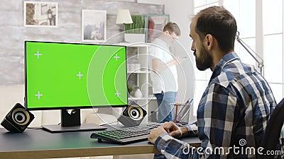 Jeune homme travaillant sur PC avec écran vert dans un salon lumineux et lumineux banque de vidéos