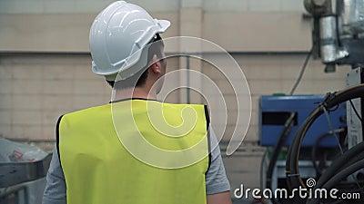 Jeune ingénieur industriel marchant à l'intérieur des équipements d'usine et vérifiant les machines de fabrication clips vidéos