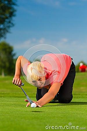 Jeune joueur de golf féminin sur le cours visant pour mis