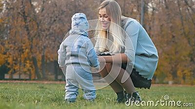 Jeune mère avec un bébé marchant en parc d'automne La mère chatouille sa chéri banque de vidéos