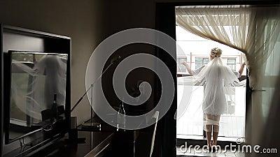 Jeune mariée avec le voile sur le balcon banque de vidéos