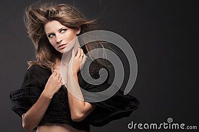 Jeune modèle de mode posant sur le fond foncé.