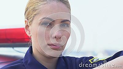 Jeune policière déterminée regardant à la caméra, profession dangereuse, sécurité banque de vidéos