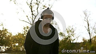 Jeune type épineux dans occasionnel noir et des écouteurs Homme de calme mettant sur ses écouteurs et musique de écoute tout en m clips vidéos