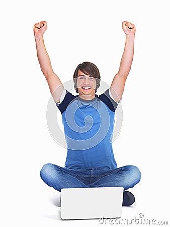 Jeune type d adolescent Excited à l aide d un ordinateur portatif
