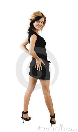 Jeune verticale de fille de beauté posant dans une robe noire mignonne
