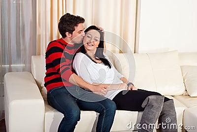 Jeunes couples affectueux sur la maison de sofa