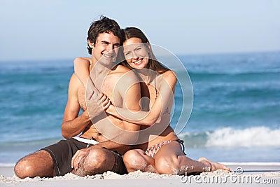 Jeunes couples détendant sur les vêtements de bain s usants de plage