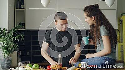 Jeunes couples heureux faisant cuire la fourmi parlant dans la cuisine à la maison Homme attirant alimentant son amie tout en cou clips vidéos