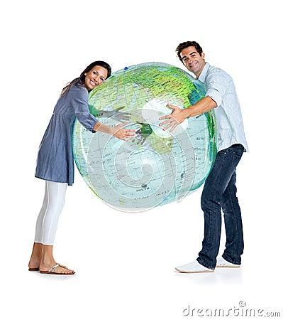 Jeunes couples heureux retenant un globe sur le blanc