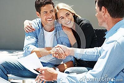 Jeunes couples heureux serrant la main avec l agent