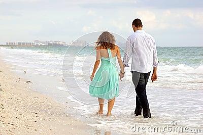 Jeunes couples marchant de pair sur le thi de plage