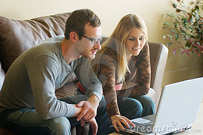 Jeunes couples regardant l ordinateur portatif
