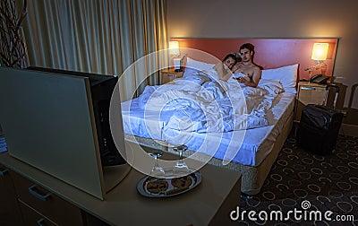jeunes couples regardant la tv dans la chambre d 39 h tel la nuit photo stock image 42296751. Black Bedroom Furniture Sets. Home Design Ideas