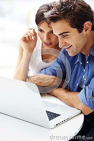 Jeunes couples travaillant ensemble sur un ordinateur portatif