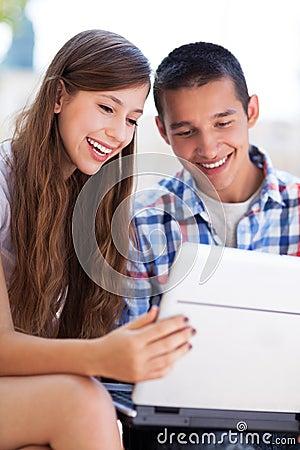 Jeunes couples utilisant l ordinateur portatif à l extérieur