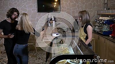Jeunes et beaux clients dans les boissons de commande d'un café et paiement avec le bitcoin de cryptocurrency utilisant leur smar clips vidéos