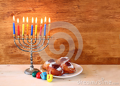Jewish holiday Hanukkah with menorah, doughnuts over wooden table ...