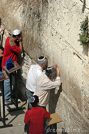 Jewish Men Pray at the Western Wall, watched by a young boy.