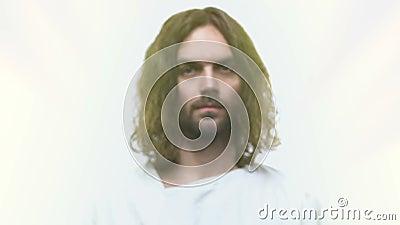 Jezus Chrystus patrzeje w kamerę na odosobnionym jaskrawym tle, religia, wiara zdjęcie wideo