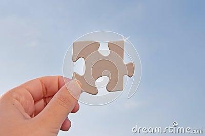 Jigsaw piece against sky