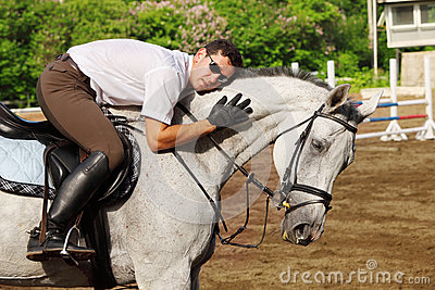 Jockey in glasses hug horse