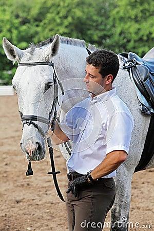 Jockey in gloves hug horse