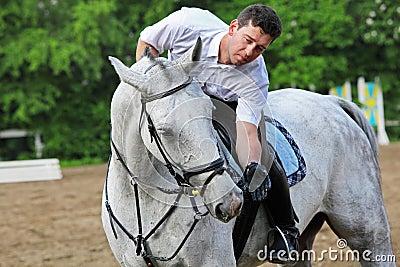 Jockey seat on horse feed from hand