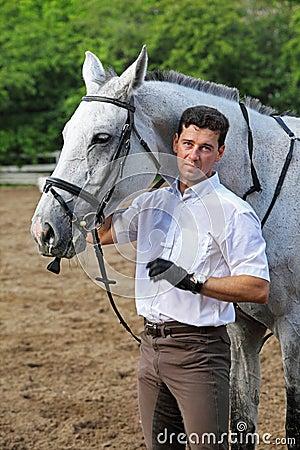 Jockey stand near horse