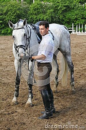 Jockey stand near horse feed him