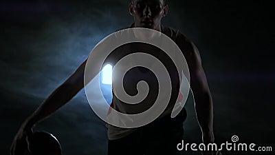 Jogador de basquetebol pingando na corte com a bola em uma sala escura com um luminoso no movimento lento no fumo video estoque