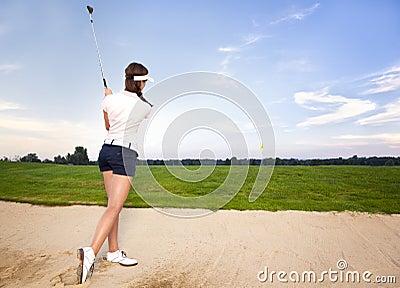 Jogador de golfe da menina no depósito que lasca a esfera.