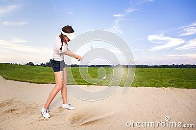 Jogador de golfe da menina que lasca a esfera no depósito.