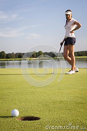 Jogador de golfe da menina que põr sobre o verde.