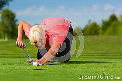 Jogador de golfe fêmea novo no curso que aponta para posto