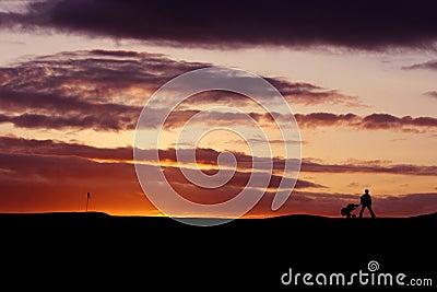 Jogador de golfe no por do sol