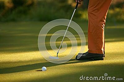 Jogador de golfe que afunda um putt