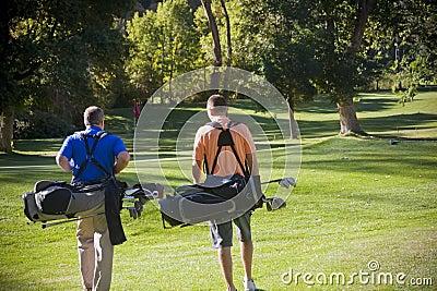 Jogadores de golfe que andam no campo de golfe