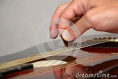 Jogando a guitarra acústica com picareta