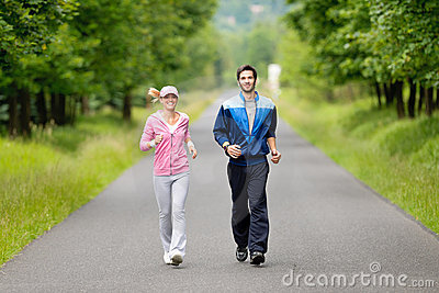 Jogging sportive young couple running park road