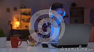 Jogo de computador de jogo adolescente Overemotional no portátil e nos petiscos comer, apego video estoque