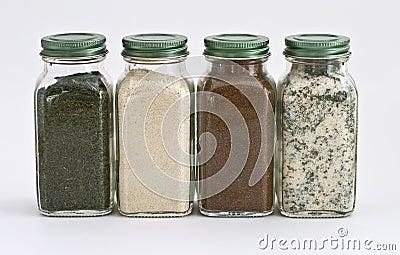 Jogo de quatro especiarias nos frascos de vidro